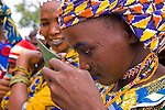 A young Fulani woman in the village of Bele Kwara in southwestern Niger applies blue makeup to her face.