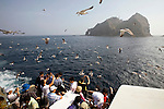 Tourists take photos of the Dokdo Islands, known to Japanese as Takeshima, sovereignty over which is disputed between Japan and South Korea, in the Sea of Japan on 22 June 2010..Photographer: Robert Gilhooly.