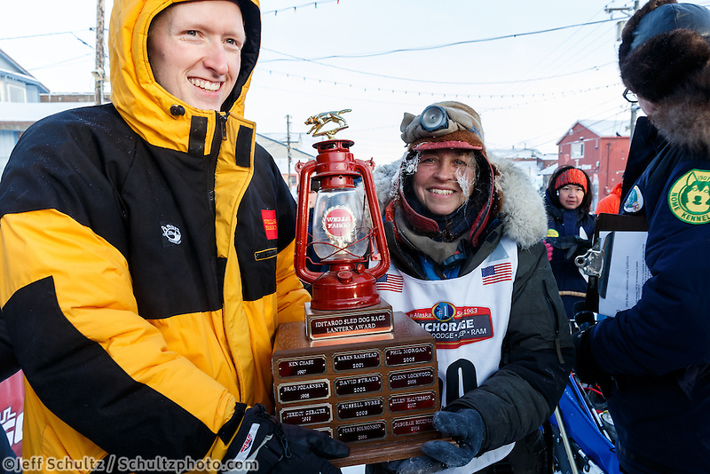 Wells Fargo Bank Nome store manager, Tyler Hull, presents Marcelle Fresineau with the red lantern last place award at the finish line shorlt after she finished in 49th place on Saturday March 15 during the 2014 Iditarod Sled Dog Race.<br /> <br /> PHOTO (c) BY JEFF SCHULTZ/IditarodPhotos.com -- REPRODUCTION PROHIBITED WITHOUT PERMISSION
