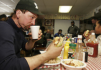 Lance Mackey chows down on a free cheeseburger Wednesday at the Takotna checkpoint