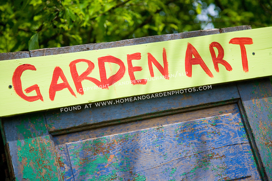 "a detail of a colorful hand-painted sign proclaiming ""garden art"" attached to an old, weathered, peeling blue green painted door"
