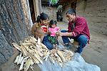 Jovita Guzman, a Maya Mam woman, pulls the grain off of corn at her home in Comitancillo, Guatemala, with help from her two-year old daughter Marilisa and her husband Maximilian Porfirio Garcia.