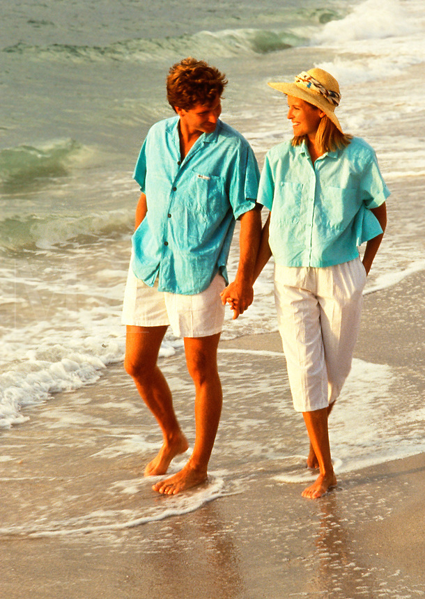 Middle-aged couple walking on beach