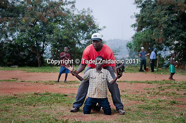 Coach George Mukhobe instructs a boy during baseball practice at sports field of St. Peter's School in Nsambya, neighbourhood in Kampala, Uganda. Coach George is one of the main forces behind baseball in Uganda.