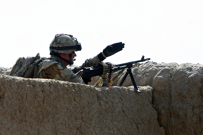 Cpl. Kevin Foster points out a Taliban position during a firefight in the village of Pashmul in Zhari district, Kandahar province, Afghanistan. Foster is with a team of Canadian soldiers mentoring Afghan troops in Zhari, where they fight daily skirmishes with insurgents. Zhari is where the hardline Taliban movement originated in the early 1990s. Sept. 29, 2008. DREW BROWN/STARS AND STRIPES