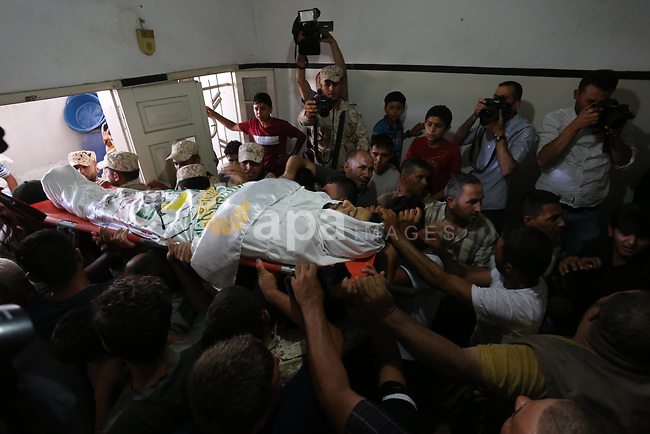 "Palestinian mourners carry the body of a Hamas security forces member, Mahmoud al-Adham, 28, into the family home during his funeral in Town of Jabaliya, northern Gaza Strip, Thursday, July 11, 2019. Hamas' armed wing said Thursday that the Israeli army ""deliberately"" fired at al-Adham, in the northern town of Beit Hanoun. Photo by Ashraf Amra"