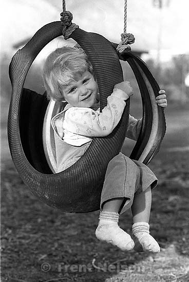 Little girl in tire swing.<br />