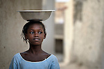 A bowl balanced on her head, a girl walks along a street in Timbuktu, the northern Mali city that was seized by Islamist fighters in 2012 and then liberated by French and Malian soldiers in early 2013. During the jihadist rule, women and girls were beaten if they went into public without being completely covered.