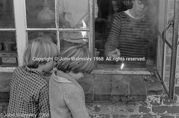 Tossing a lighted taper out of the window, Science laboratory, Summerhill school, Leiston, Suffolk, UK. 1968.