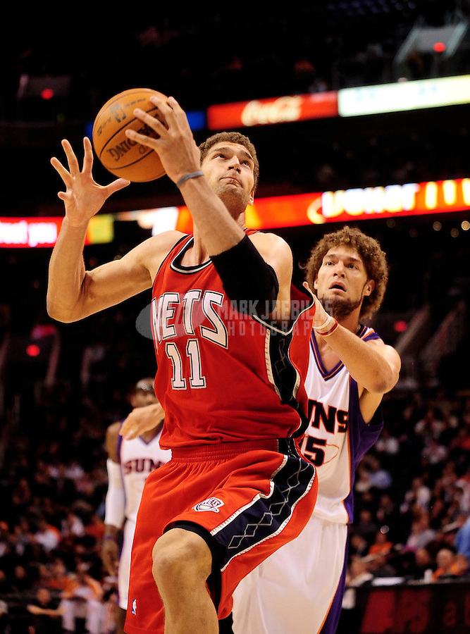 Jan. 20, 2010; Phoenix, AZ, USA; New Jersey Nets center (11) Brook Lopez drives to the basket past brother, Phoenix Suns center (15) Robin Lopez in the second half at the US Airways Center. The Suns defeated the Nets 118-94. Mandatory Credit: Mark J. Rebilas-