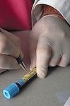 gloved hand writing on blood sample vial