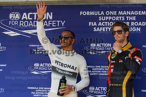 Petronas Mercedes F1 Formula One driver Lewis Hamilton (L) of Great Britain and Lotus F1 Formula One driver Romain Grosjean (R) of Switzerland celebrate their victory in the qualifier of the Hungarian F1 Grand Prix in Mogyorod (about 20km north-east from capital city Budapest), Hungary on July 27, 2013. ATTILA VOLGYI