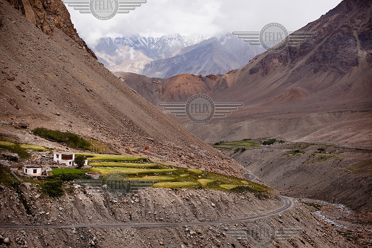 A terraced farm, common in this region near the Khardung La Pass to the Nubra Valley. The pass is the highest motorable road in the world at 18,380 ft. Mountains in the background.