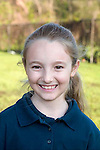 Caucasian blonde second grade smiling female in school uniform outdoors