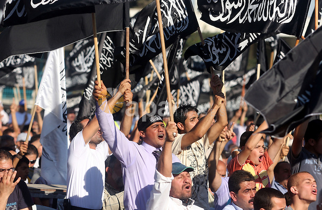"Palestinian supporters of Hizb ut-Tahrir or the Islamic Liberation Party, chant slogans and wave black and white flags with the religous writing ""There is no God but God, and Mohammed is his prophet"" during a rally in the West Bank city of Ramallah, on July 7, 2012. The Islamic Liberation Party, which calls for the return of the Islamic caliphate and the establishment of an Islamic states, has no military power in the Palestinian territories and its goal is to join all Muslim countries under one nation. Photo by Issam Rimawi"
