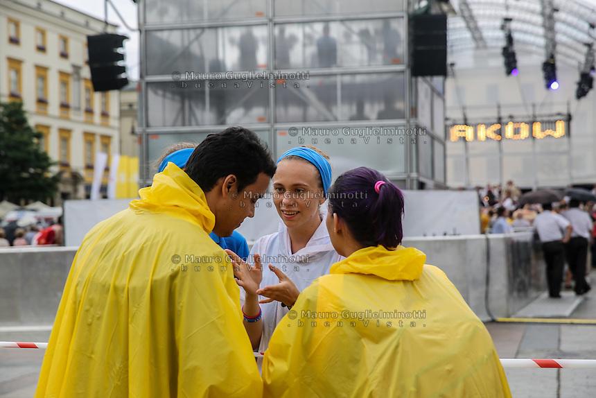 World Youth day Krakow 2016<br /> una volontaria d&agrave; informazioni a due pellegrini in impermeabile giallo