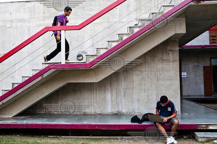 A law student walks up stairs to his hostel room while another student works on his laptop at the Jindal Global University in Sonepat.
