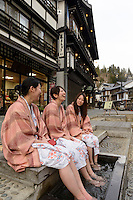 Visitors enjoying a foot bath on the main street. Ginzan Onsen, Yamagata Prefecture, Japan, April 12, 2016. Once a sliver-mining town, Ginzan Onsen in Yamagata Prefecture is now one of Japan's best-known and most picturesque hot spring resorts. Its Taisho-period architecture and retro atmosphere is said to have been an inspiration for Hayao Miyazaki's Oscar-winning animated film, Spirited Away.