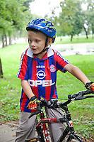 Polish boy age 8 riding bike wearing a bicycle helmet and gloves. Paderewski Park Rzeczyca Central Poland