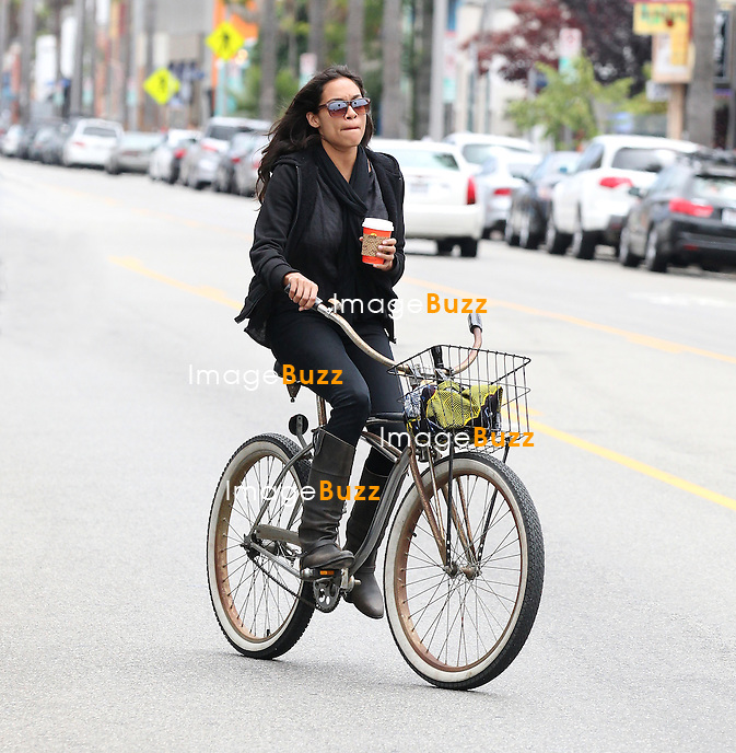 Rosario Dawson drinking her coffee while riding her beach cruiser bicycle in Venice Beach. Los Angeles, July 7, 2012..EXCLUSIVE PHOTOS
