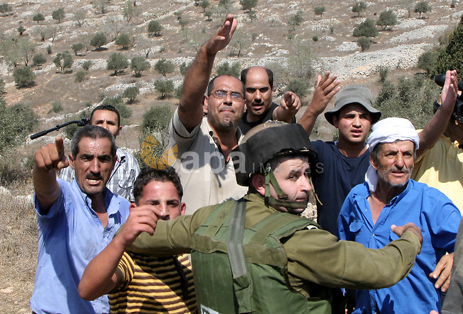 Israeli soldiers prevent Palestinian farmers from scuffling with Israeli settlers during clashes between residents of the Israeli Bracha settlement and Palestinian farmers from the West Bank Burin village on September 21, 2010. The fight broke when settlers tried to collect olives from Palestinian land. Photo by Wagdi Eshtayah