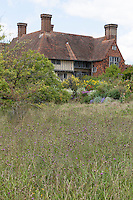 The orchard at Great Dixter with the 15th century house behind with mature border
