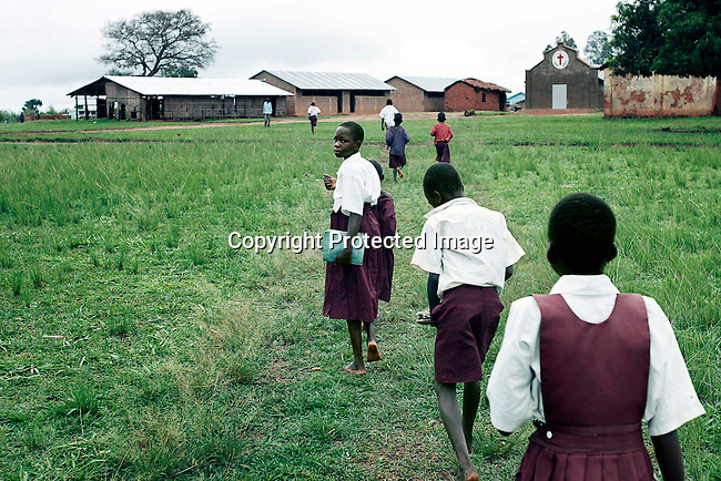LALIYA, UGANDA MAY 27: Susan Labol (c)), age 10, arrives at St. Martine Primary School on May 27, 2005 in Laliya, Uganda. Susan is a night commuter, one of about 20,000 children that sleep in Gulu town, as they are afraid of being abducted by the Lord's Resistance Army (LRA). The rebel group has brought terror to Northern Uganda for almost twenty years, fighting the Ugandan government. The victims are usually children, which are abducted and used as child soldiers and sex slaves. Susan walks 1,5 hour from her home every day to sleep at Noah's Arch, an NGO housing children in Gulu. She is too afraid to sleep in the village as an older sister was earlier abducted. She walks a further 30 minutes every day to attend school in a nearby village. .