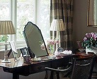 An antique mirror and table have been combined to create a dressing table displaying a collection of family photographs flanked by matching table lamps