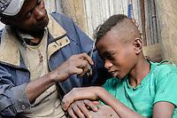 MADAGASCAR, village Tanambao North, tribe Tanala, father cut the hair of his son / MADAGASKAR Mananjary, Vohilava, Dorf Tanambao Nord wo Menschen der Volksgruppe der Tanala leben, Vater schneidet Junge die Haare