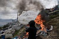 BOGOTA - COLOMBIA, 29-05-2020: Joven quema las pertenencias que no puede llevar con él,  después de ser notificado de su desalojo por agentes de la alcaldía local. Mas de 200 familias terminan el proceso de desalojo en el predio La Estancia al sur de Bogotá quedando sin ninguna ayuda ni un techo donde vivir durante la cuarentena total en el territorio colombiano causada por la pandemia  del Coronavirus, COVID-19. / Young man burns belongings that she cannot carry with her, after being notified of her eviction by agents of the local mayor's office. More than 200 families are evicted from La Estancia farm at south of Bogota city and they left withoput any help and shelter to live during total quarantine in Colombian territory caused by the Coronavirus pandemic, COVID-19. Photo: VizzorImage / Mariano Vimos / Cont