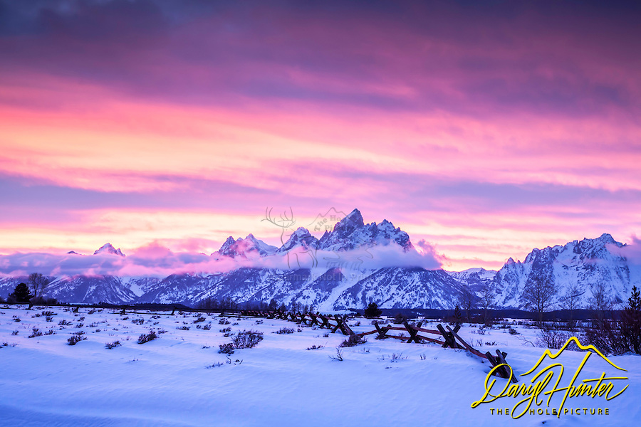 Winter sunset, Grand Teton Park.  Undulating ridges and a buckrail fence accent a psychedelic  sky<br />