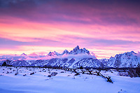 Winter sunset, Grand Teton Park.  Undulating ridges and a buckrail fence accent a psychedelic  sky