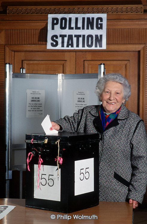 Putting a ballot paper in a ballot box (posed by model).