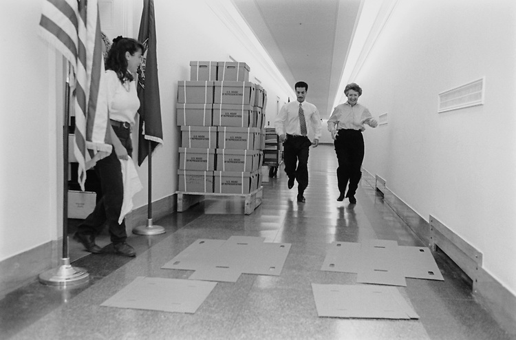 L.C. Vicki Meizger drops the flag and gets out of the way as Staff Assistant Omar Jabara and Administrative Assistant Maggi Luca race to assemble their boxes. (Photo by CQ Roll Call via Getty Images)