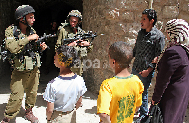 Israeli soldiers stop a Palestinian man as a group of Jewish settlers gather in the city center of the West Bank town of Hebron on May 08, 2010. Photo by Najeh Hashlamoun
