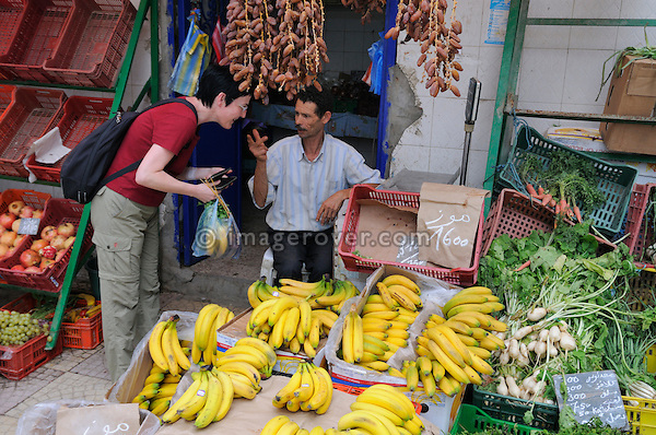 Africa, Tunisia, Nabeul. Desert tourist Kerstin shopping for fruits in the centre of Nabeul. --- No releases available, but releases may not be needed for certain uses. --- Info: Image belongs to a series of photographs taken on a journey to southern Tunisia in North Africa in October 2010. The trip was undertaken by 10 people driving 5 historic Series Land Rover vehicles from the 1960's and 1970's. Most of the journey's time was spent in the Sahara desert, especially in the area around Douz, Tembaine, Ksar Ghilane on the eastern edge of the Grand Erg Oriental.