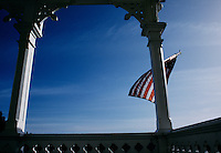 Blue sky backdrop for an American flag that blows in the ocean breeze on the front porch of a Victorian home in quaint, historic Mendocino.