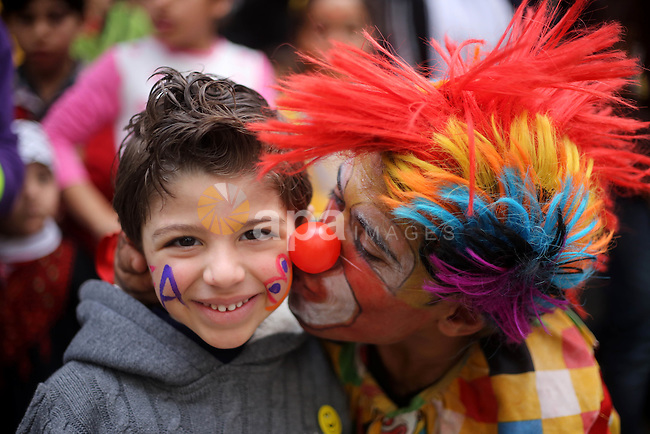 A clown kisses a Palestinian boy during a street game organised by volunteers of the Friday of Joy Initiative, in al-Shati refugee camp, in Gaza city, February 6, 2015. Ten Palestinian volunteers organise street games, painting and drama, every Friday afternoon in the streets of  refugee camps and provide outlets for the children's energy with organised games, dancing and singing, which gives extra psycho-social support to vulnerable children. Photo by Khaled al-Sabbah