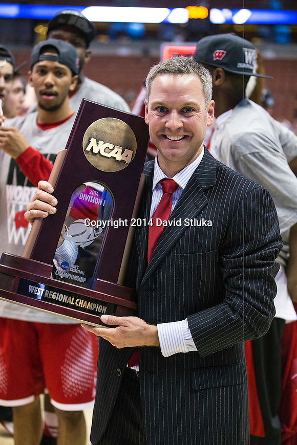 Wisconsin Badgers basketball director of communications Patrick Herb handles the West Regional Trophy after the Western Regional Final NCAA college basketball tournament game against the Arizona Wildcats Saturday, March 29, 2014 in Anaheim, California. The Badgers won 64-63 (OT). (Photo by David Stluka)