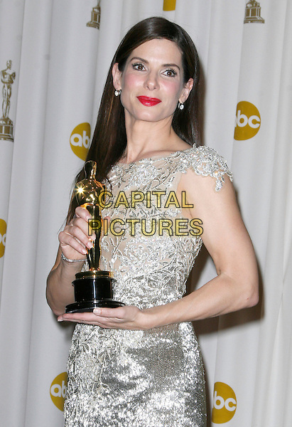 SANDRA BULLOCK.The 82nd Annual Academy Awards held aat The Kodak Theatre in Hollywood, California, USA..March 7th, 2010.oscars half length silver gold beige silk satin pink lipstick dress winner trophy dress.CAP/EAST.©Eastman/Capital Pictures.