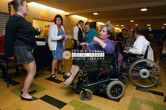 Members and guests enjoying dancing at a social evening organised by a disability friendship club,