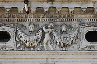 Sculpted frieze of putti above the first floor Ionic arcade of the Biblioteca Nazionale Marciana, or National Library of St Mark's, built in Renaissance style in 1537-53 by Jacopo Sansovino, then extended by Vincenzo Scamozzi in 1588, on the Piazzetta San Marco, between the Piazza San Marco and the Venetian lagoon, Venice, Italy. The columns are topped with Ionic capitals and the spandrel figures are angels in classical or all'antica style, and above, puttis hold decorative garlands, with lion's heads representing St Mark the Evangelist, patron saint of Venice. The 2-storey building is lined with a Doric arcade on the ground floor and Ionic arcade on the first floor, with sculptural decoration and a line of rooftop statues. The library houses an important collection of classical, Oriental and medieval codices and manuscripts. The historical centre of Venice is listed as a UNESCO World Heritage Site. Picture by Manuel Cohen