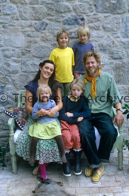 Portrait of Henry and Flora Brudenell-Bruce and their four children on a bench outside their Devon home