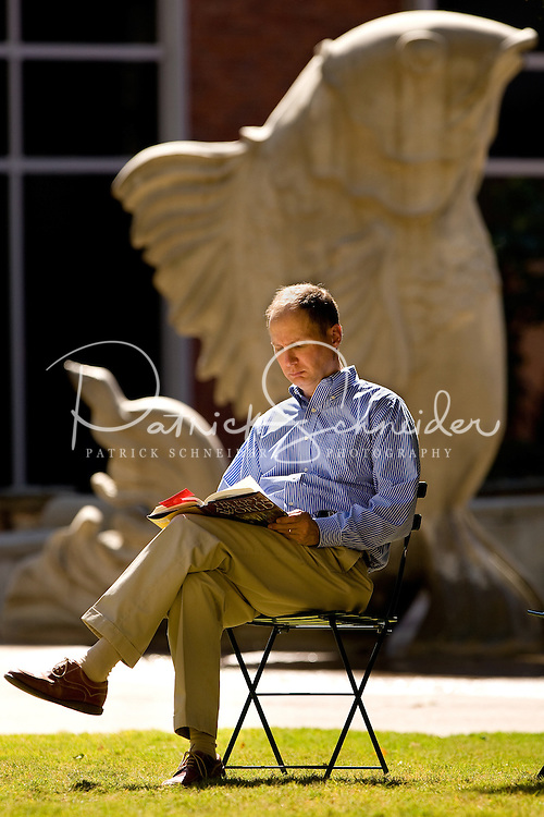 A professional businessman reads a book on the green in uptown Charlotte, NC.