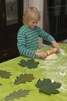 Kinder basteln Blattkacheln aus Salzteig, Junge rollt den Salzteig aus