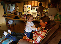 "Josie sits on her mother's lap while Kitty puts her feet up to rest after the morning training a mustang.<br /> <br /> Kitty Lauman trains mustangs--as she says working with the horses, not against them.  They have a ranch in Prineville, OR.<br /> <br /> Kitty, her husband Rick and their children, Josie, 2 ½,  and Tanner, 5,  ride mustangs. Kitty Lauman started her career as a horse trainer at the tender age of nine, under the guidance of her grandfather, John Sharp. <br /> <br /> She later became a top Pee Wee and High School Rodeo contestant, competing in barrel racing and cutting, among other events. Despite her mother's assertion that ""horse training isn't a real job,"" Kitty managed to make a living as a trainer after high school (and her mom now helps out with the business!) <br /> <br /> Kitty won the title of Miss Rodeo Oregon in 1994, and since then, has continued to expand her horse training knowledge and experience.  She placed second in the Extreme Mustang Makeover, a national competition in 2008."