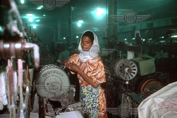 Worker at the Asmara textile factory, the largest industrial employer in the country. The company was originally Italian-owned. Much of the machinery, like the looms in this production line, is now well past its best.