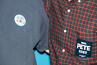 """A man wears a campaign button reading """"Chasten's Husband / President 2020"""" as Chasten Buttigieg, husband of Democratic presidential candidate and South Bend, Ind., mayor Pete Buttigieg, speaks at a Buttigieg campaign office opening in Concord, New Hampshire, on Thu., September 5, 2019."""