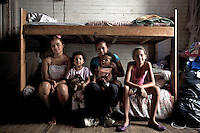 Buenos Aires, Argentina...Interior de una casa de Isla Maciel. Claudia y su familia..El Riachuelo no es solo un río de ochenta kilómetros de largo. También es un símbolo de Buenos Aires.  Atraviesa la historia de la ciudad, y la atraviesa geográficamente. .En casi todo su recorrido, el Riachuelo tiene 0% de Oxígeno en el agua. Está ahogado en si mismo, en gran parte gracias a las 4100 industrias que arrojan sus desechos sobre su cauce. ..Inside a house in Maciel Island. Claudia and her family..The Riachuelo river is a symbol of Buenos Aires. It passes through the history of the city and it also crosses it geographically. As rare as it may seem, most of the Riachuelo has 0% of oxygen in the water. Mainly, thanks to the over 4100 industries that throw their wastes there. ..Maison dans l île Maciel. Claudia et sa famille..Le fleuve Riachuelo est un symbole de Buenos Aires.Il traverse l'histoire de la ville et il le traverse aussi géographiquement. Aussi rare qu'il peut sembler, la plupart des Riachuelo ont 0 % d'oxygène dans l'eau, sûr tout à cause des déchets de plus de 4100 industries. Le fleuve est noyé sur soi même.