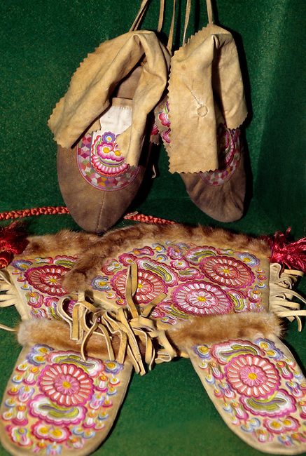 Pair of moose hide Cree moccasins and gloves that have been intricatedly embroidered with colorful threads for decoration.